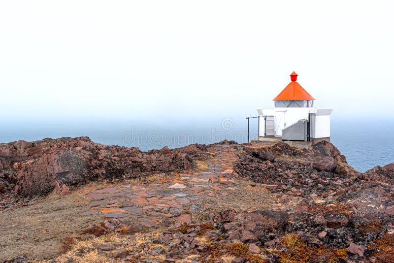 有一个红顶和一条石小径的海烽火台在有雾的海的岩石边缘 库存图片