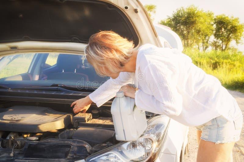 有一个罐头的美丽的白肤金发的女孩油参与在乡下公路的汽车修理和落日的光芒 库存照片