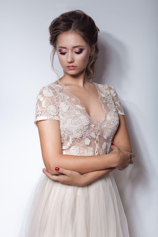 有一个美丽的新娘的美丽的逗人喜爱的甜女孩有在现代时髦婚礼礼服的明亮的构成晚上婚礼发型的在t 免版税图库摄影