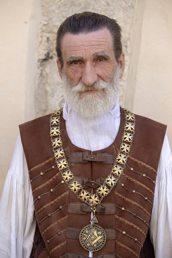 有一个美丽的灰色胡子的绅士在市中心利沃夫州,乌克兰邀请游人进入在街道上的餐馆 库存图片