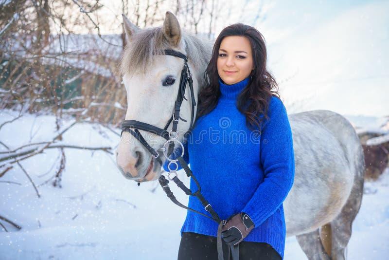 有一个美好的冬天白马的一年轻女人 库存照片