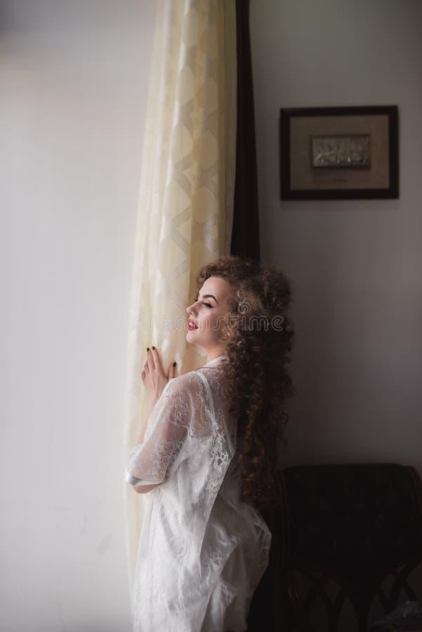 有一个美好的图的年轻嫩和美丽的女孩支持窗口 免版税库存照片