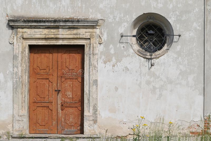 有一个老木门和一个小窗口的石墙 免版税库存图片