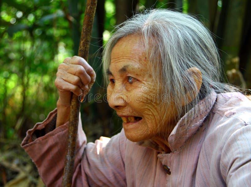 有一个职员的年长中国妇女在她的手上 免版税库存照片