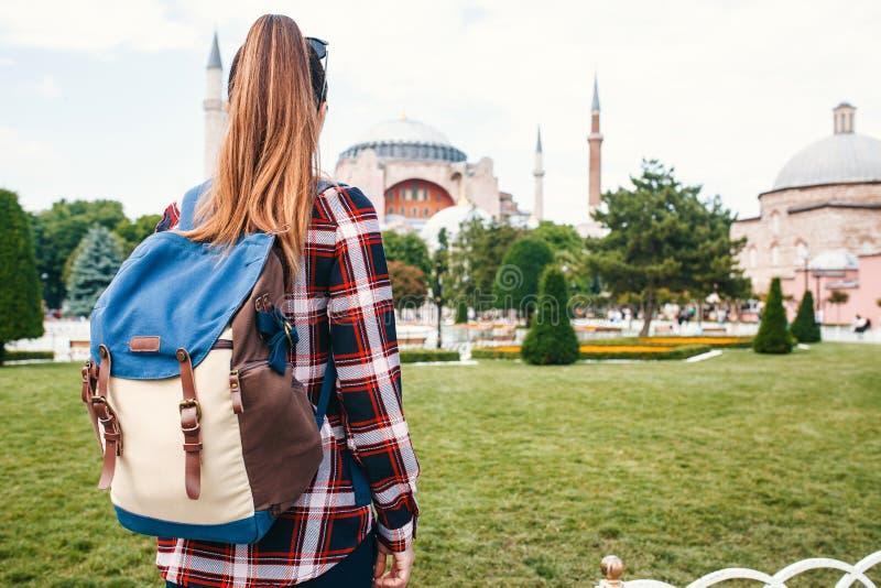 有一个背包的一个年轻旅客女孩在著名Aya索非亚清真寺旁边的Sultanahmet广场在伊斯坦布尔在土耳其 免版税库存照片
