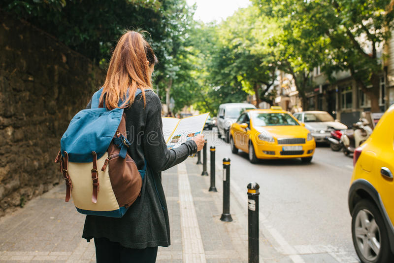 有一个背包的一个年轻旅游女孩在一个大城市观看一张地图 旅途 观光 旅行 库存照片