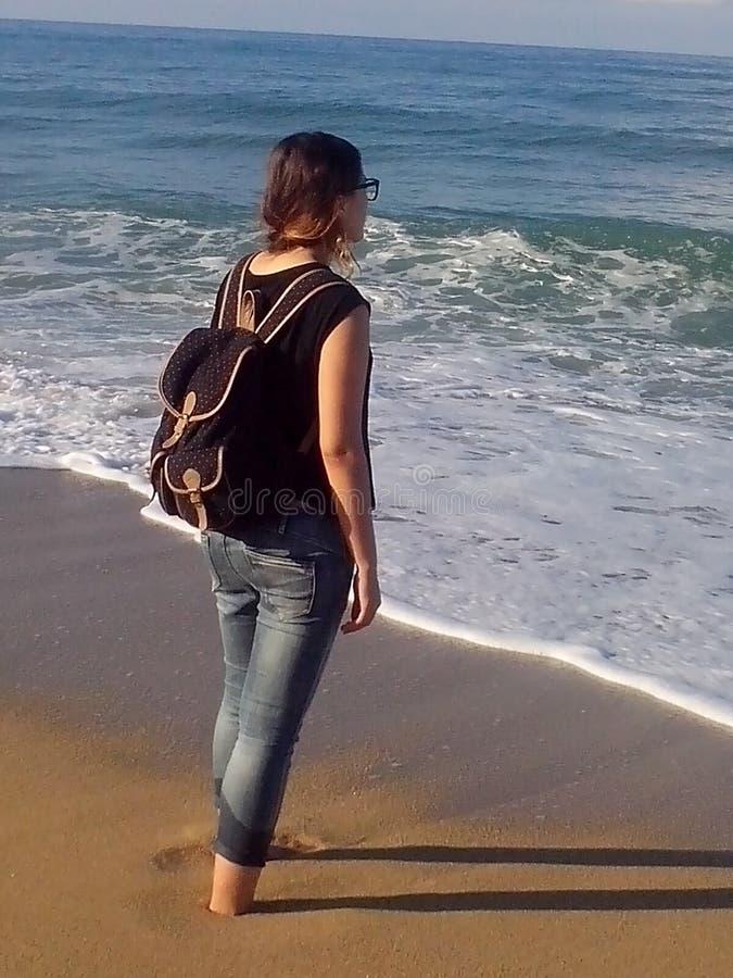 有一个背包的女孩在她站立在海滩 免版税图库摄影