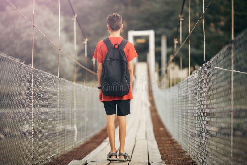 有一个背包的少年在山,男孩穿过吊桥的一条山河 图库摄影