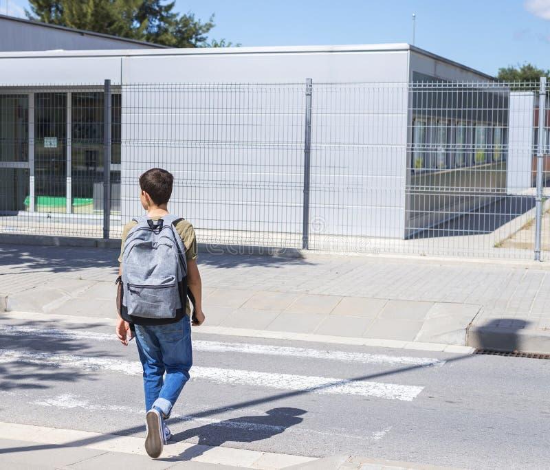 有一个背包的少年男生在他的后面走到学校的 库存照片
