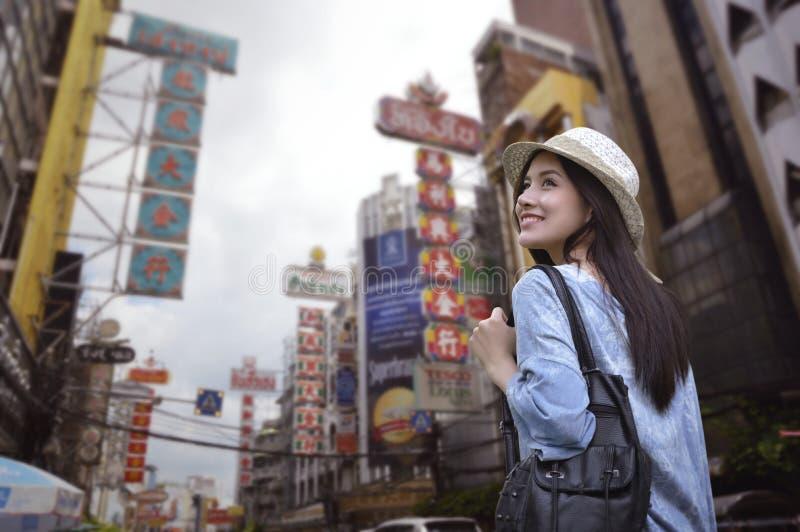 有一个背包的年轻亚裔妇女旅客在她的肩膀和旅行帽子 库存图片