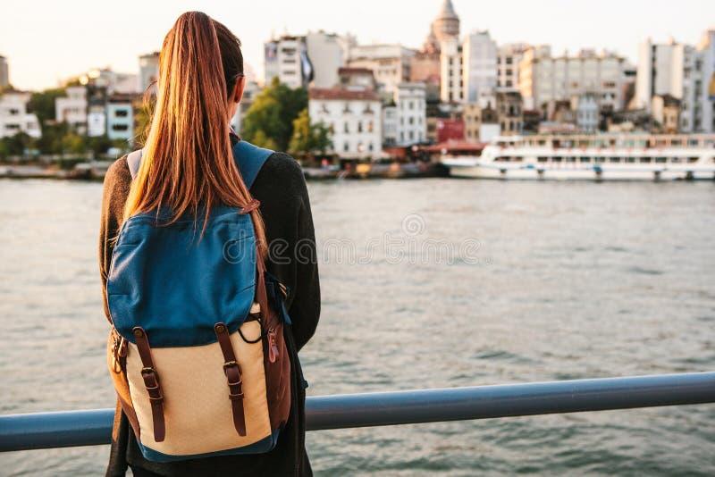 有一个背包的年轻美丽的旅游女孩在Bosphorus旁边的日落在伊斯坦布尔背景  火鸡 其它 免版税库存照片
