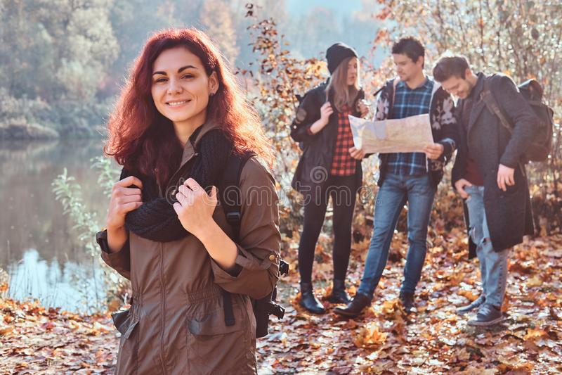 有一个背包的迷人的红头发人女孩在前景和看地图和计划在的一个小组朋友远足 库存图片