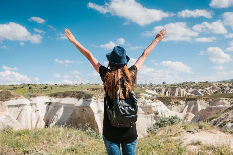 有一个背包的年轻美丽的旅行女孩在小山顶部在卡帕多细亚,土耳其 旅行,成功,自由 免版税库存图片