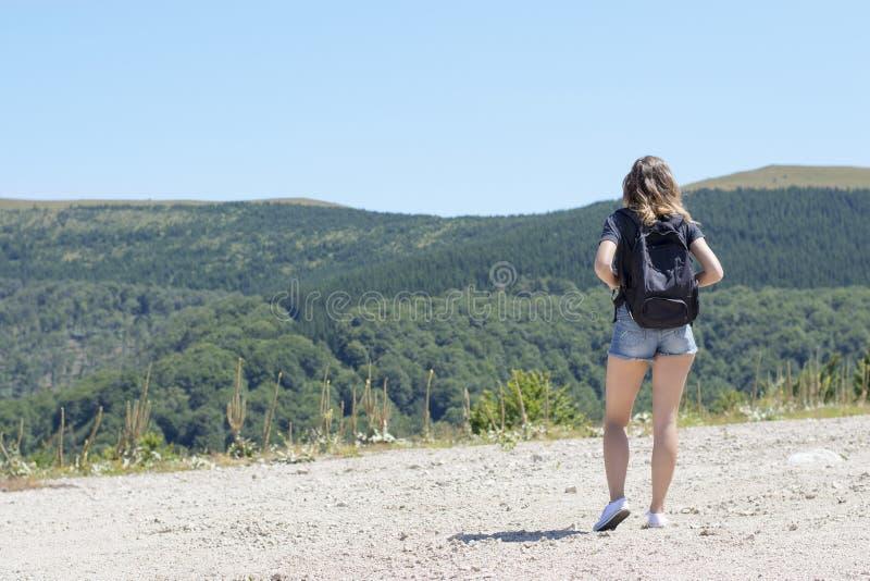有一个背包的年轻,美丽的女孩在她,站立在t 库存图片