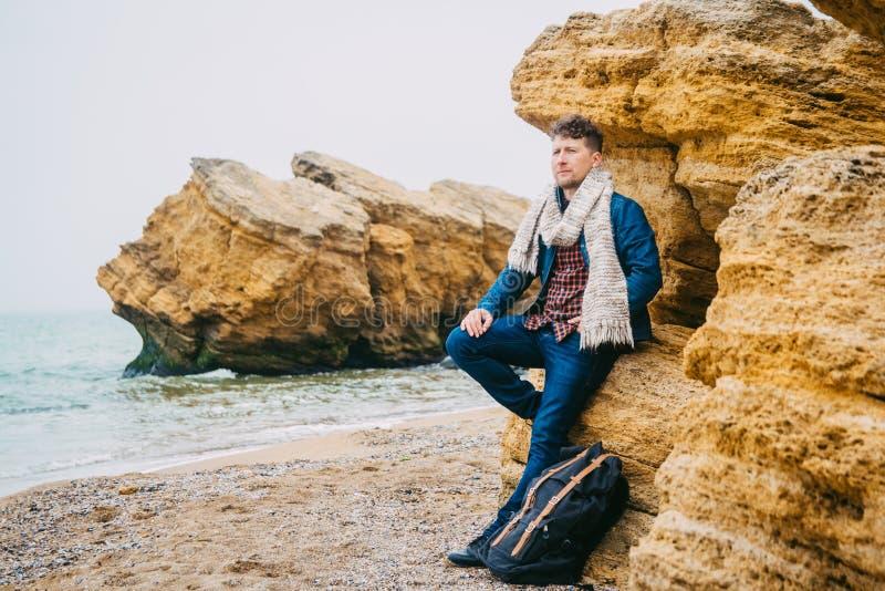 有一个背包身分的年轻人旅客在反对美丽的海有波浪的,一时髦行家男孩摆在的一个岩石 免版税库存照片