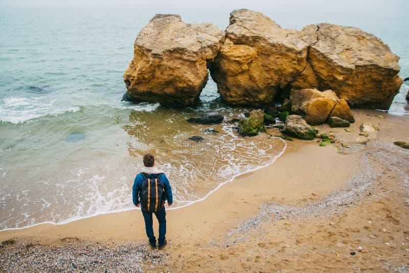 有一个背包身分的旅客在反对美丽的海的一个岩石附近有波浪的,摆在a附近的一个时髦的行家男孩 免版税图库摄影