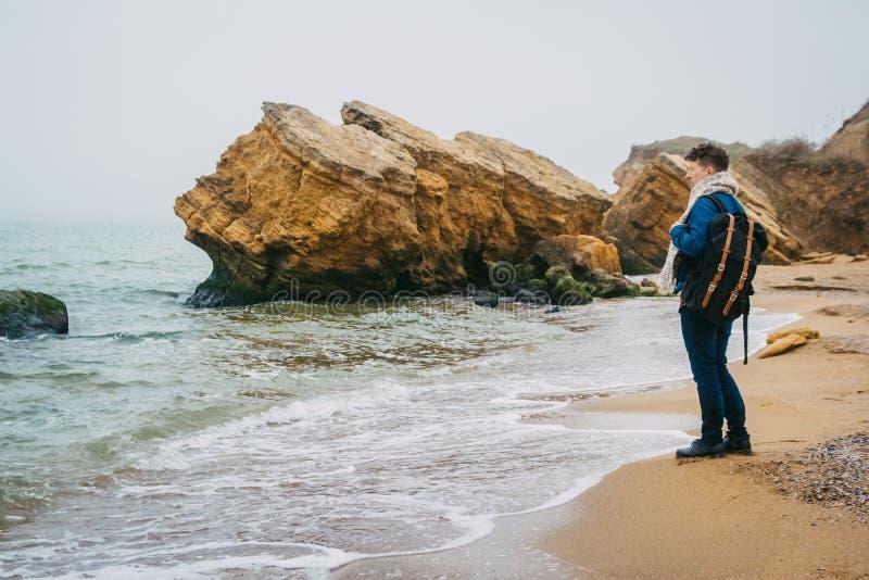 有一个背包身分的旅客在反对美丽的海的一个岩石附近有波浪的,摆在a附近的一个时髦的行家男孩 图库摄影