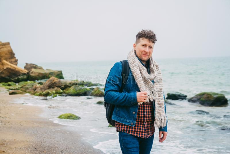 有一个背包身分的旅客在有波浪的美丽的海附近,摆在镇静海洋附近的一个时髦的行家男孩在期间 库存照片