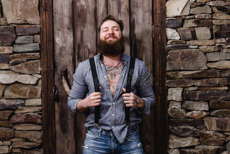 有一个胡子和纹身花刺的滑稽的残酷人在时髦的便服穿戴的他的手上在背景摆在  免版税库存照片