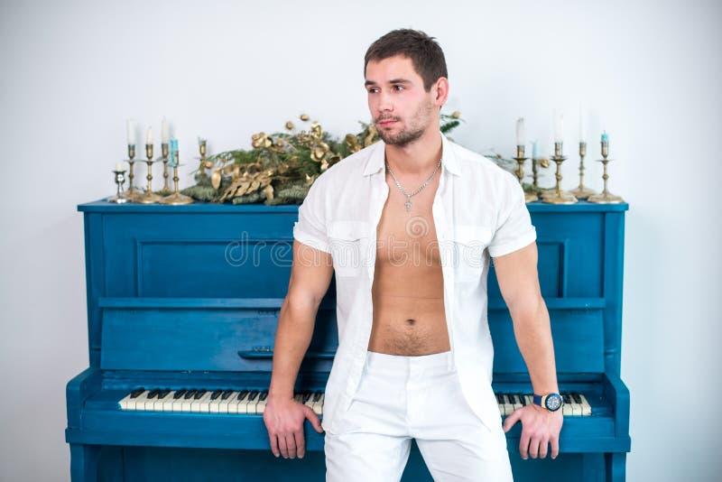 有一个胡子的体贴,英俊的人在以钢琴,有光秃的躯干的一件被锉的衬衣为背景的白色衣裳 免版税库存照片
