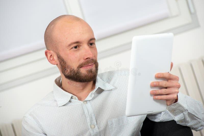 有一个胡子的年轻人使用一种数字片剂 免版税库存图片