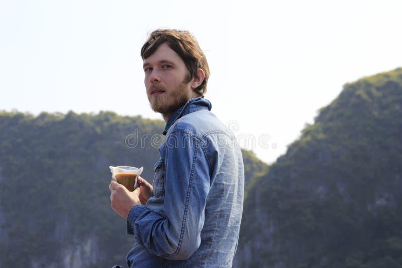 有一个胡子的年轻白可爱的白肤金发的人在一件蓝色牛仔布衬衣周道地站立与一杯咖啡 免版税图库摄影