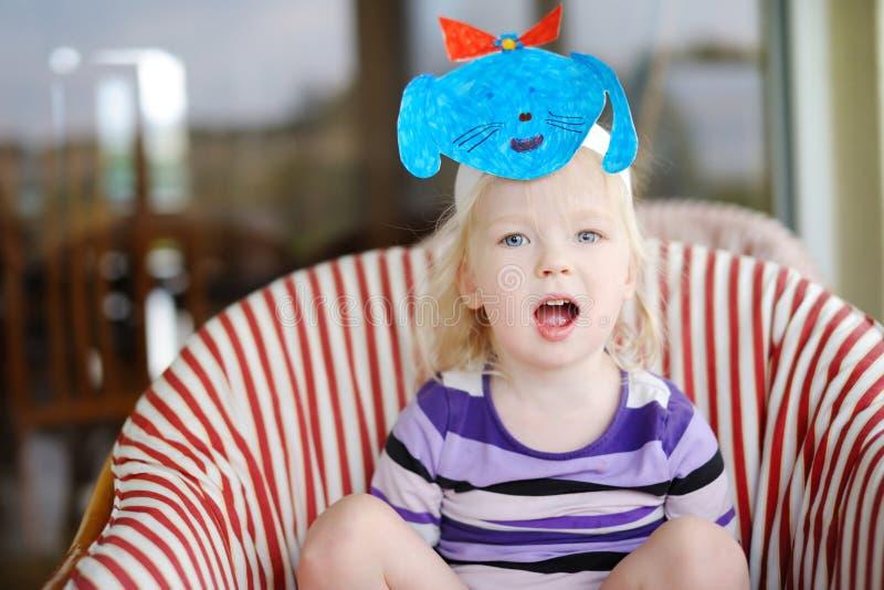 有一个自制小狗面具的逗人喜爱的矮小的小孩女孩 库存照片