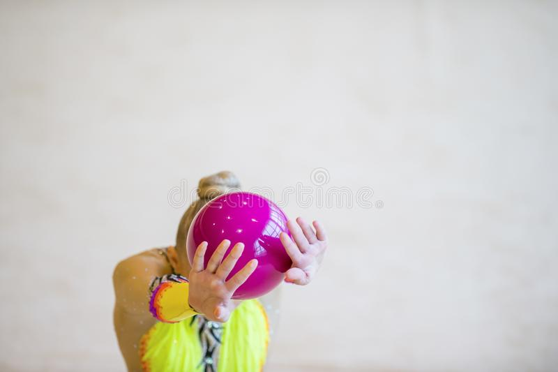 有一个节奏体操桃红色球的女孩 在acroba的灵活性 库存照片