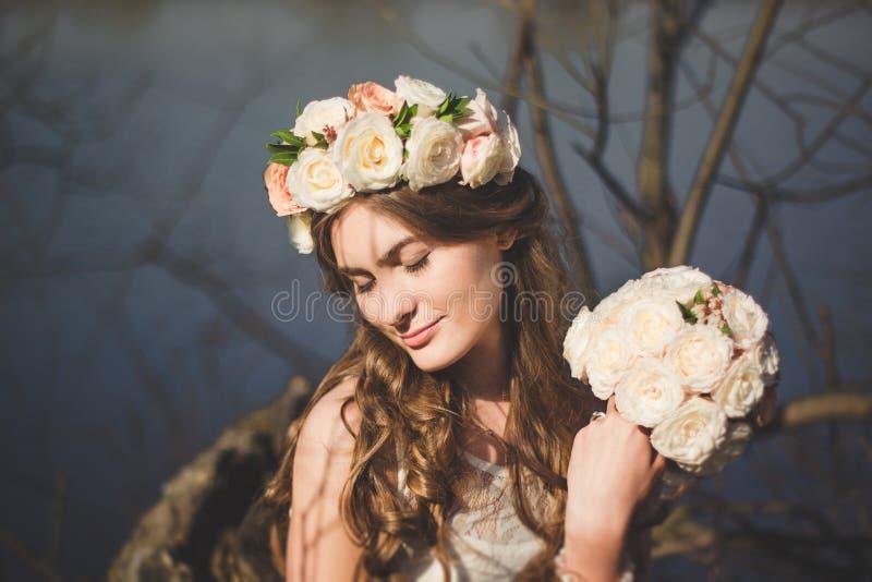 有一个花卉花圈的女孩在摆在树附近的头 图库摄影