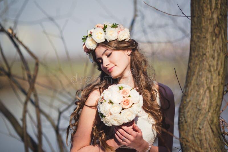 有一个花卉花圈的女孩在摆在湖的头 免版税库存照片