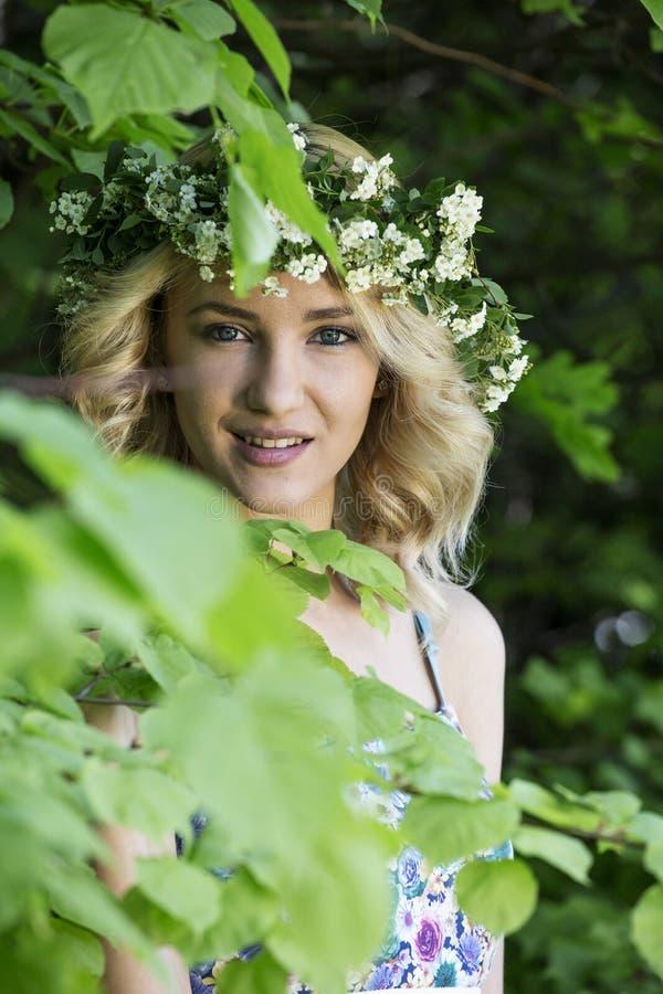 有一个花圈的美丽的性感的微笑的女孩在他的头在春天公园 免版税图库摄影