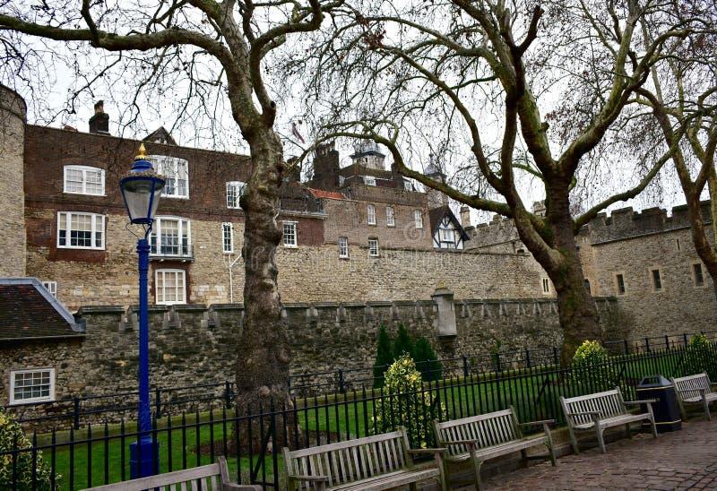 有一个蓝色和金黄街灯、树和长木凳的伦敦塔 大厦王国伦敦老塔团结的维多利亚 库存照片