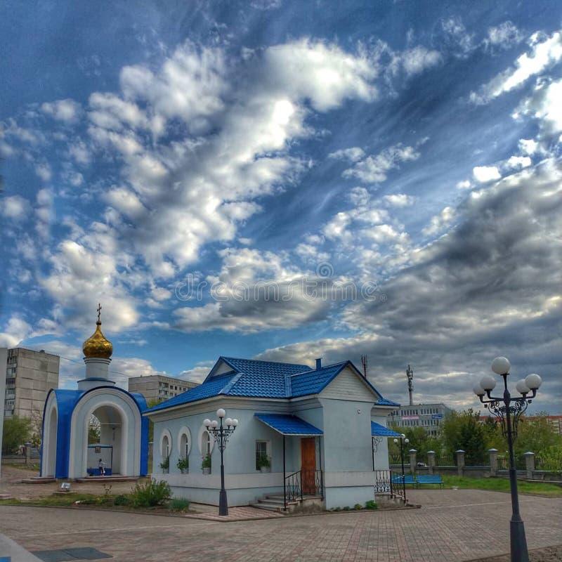 有一个蓝色屋顶的一个小屋,与Golden Dome的一个大厦和与白色云彩的一明亮的天空蔚蓝,索斯诺沃博尔斯克,克拉斯诺亚尔斯克r 库存照片
