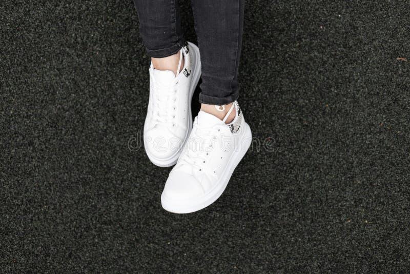有一个蛇样式的时髦的皮革白色运动鞋在黑背景 女性腿特写镜头  时髦的女人的鞋子 免版税库存图片