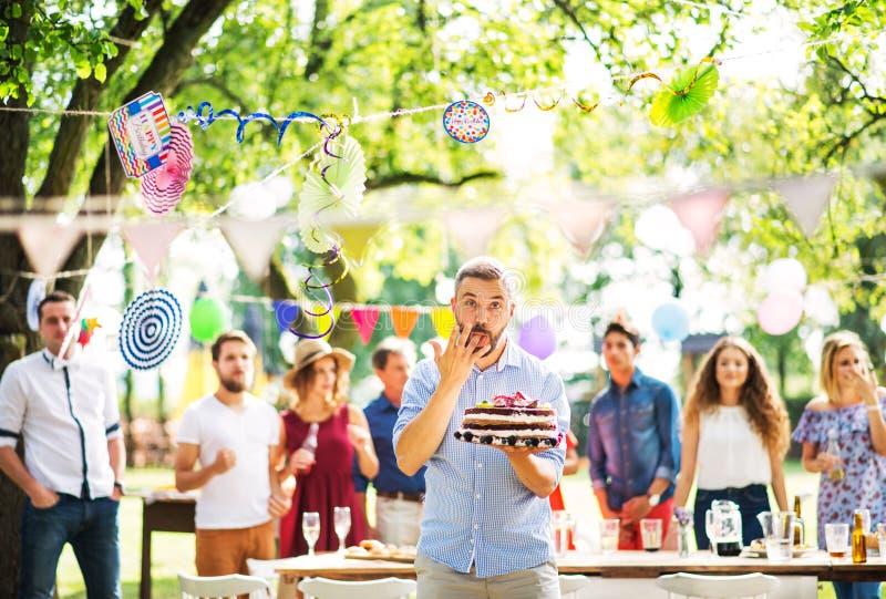 有一个蛋糕的人在外面家庭庆祝或游园会,舔他的手指 免版税库存图片