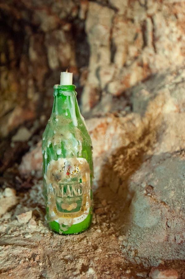 有一个蜡烛的老啤酒瓶在与蜡的顶面水滴 免版税库存照片