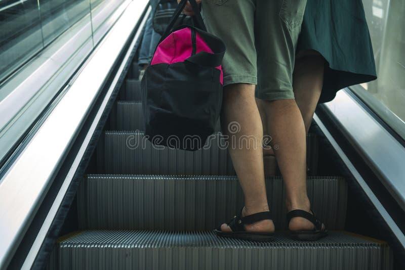 有一个袋子的一个人在旅行在自动扶梯被明白 免版税库存照片