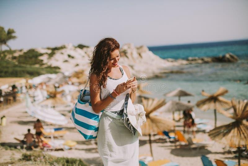 有一个袋子的俏丽的年轻女人使用在海滩的手机 免版税图库摄影