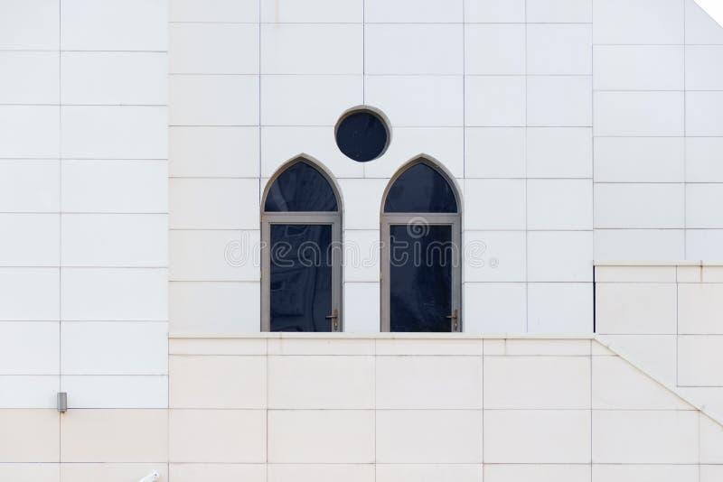 有一个被成拱形的和圆的窗口的,外部的细节修造,都市几何白色墙壁 库存图片