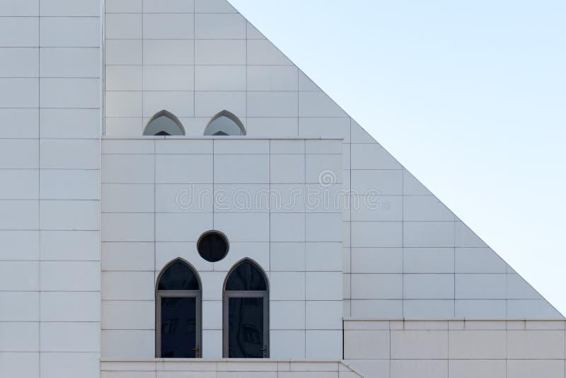 有一个被成拱形的和圆的窗口的,外部的细节修造,都市几何白色墙壁 免版税库存照片