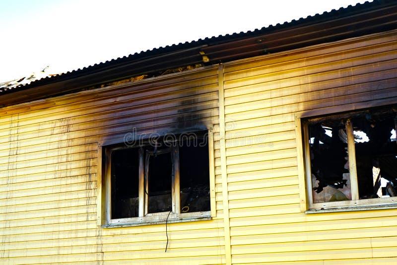 有一个被烧焦的墙壁和残破的窗口的被烧的商店 火的后果 库存图片