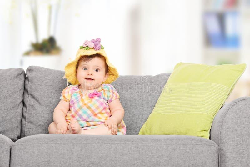 有一个被编织的帽子的逗人喜爱的女婴坐沙发 图库摄影