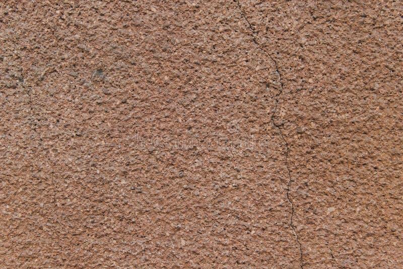 有一个裂缝的布朗粗砺的墙壁对此 库存照片