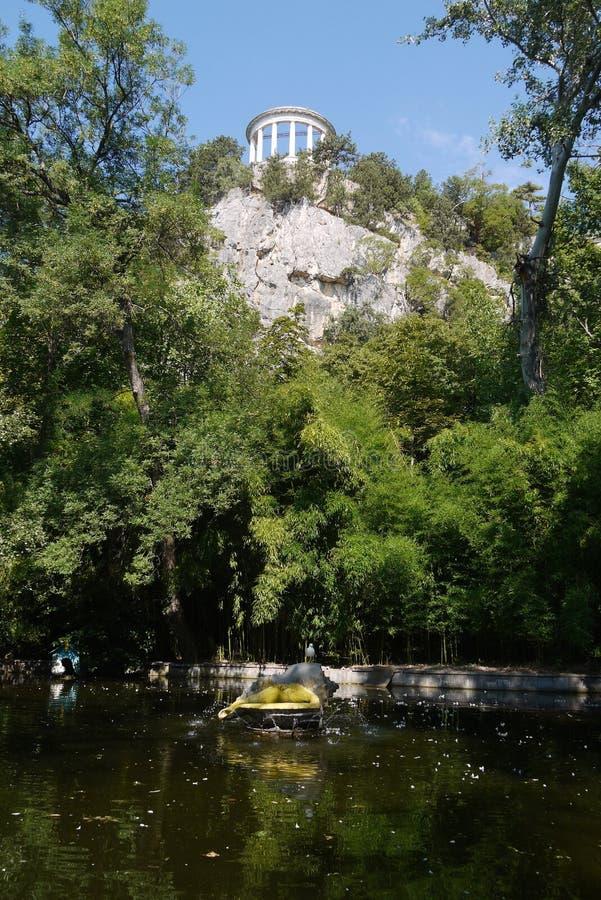 有一个装饰喷泉的绿色湖在高落矶山脉的背景与一个白色观测台的 库存照片