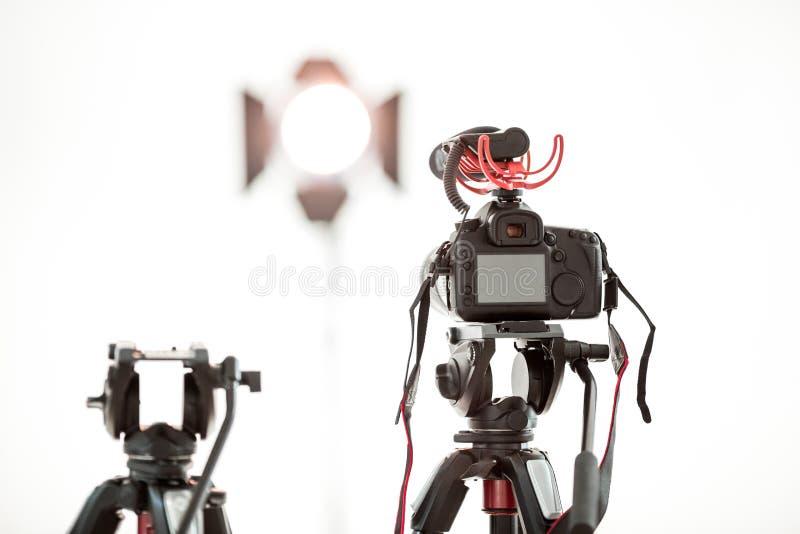 有一个话筒的一数码摄像机在白色背景,一盏明亮的聚光灯的一个三脚架在背景中 免版税库存图片