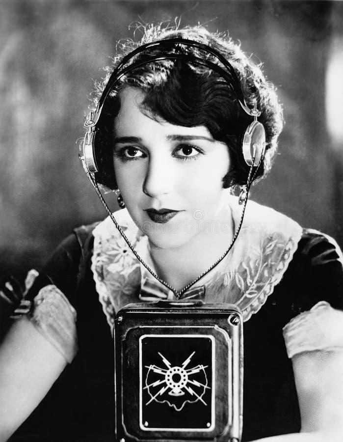 有一个话筒的妇女佩带的耳机在她前面(所有人被描述不更长生存,并且庄园不存在 补助 免版税库存照片