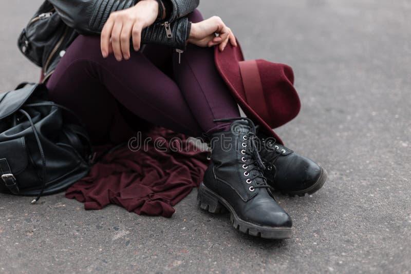有一个豪华葡萄酒紫色帽子的年轻女人在皮革时兴的黑起动的时髦长裤 时髦的妇女的头饰 图库摄影