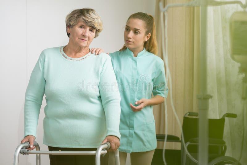 有一个资深夫人的生理治疗师 免版税库存图片