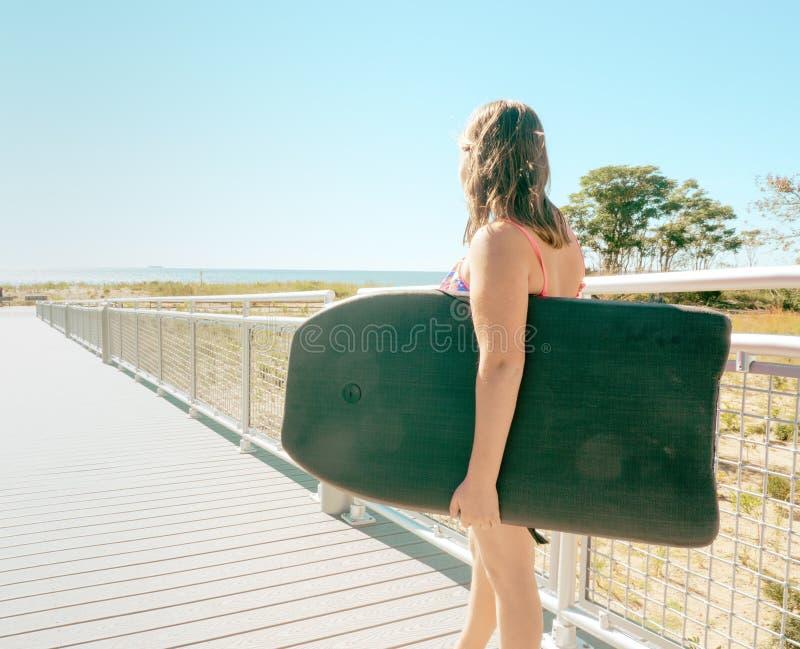 有一个身体板的女孩在海洋附近 库存图片