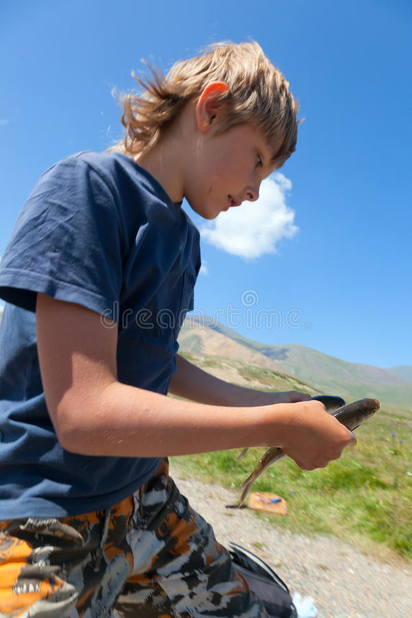 有一个转动的抓住河鳟的男孩 库存图片